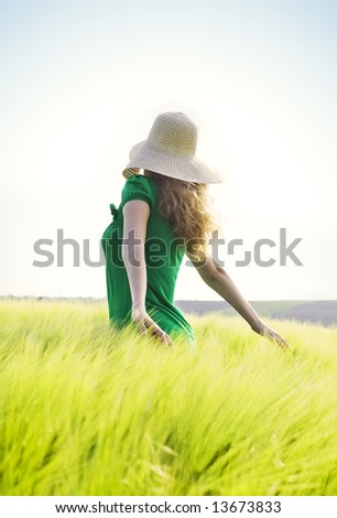 blond girl with big hat walking through a green wheat field against blue sky - stock photo