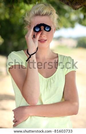 Blond girl with binoculars - stock photo