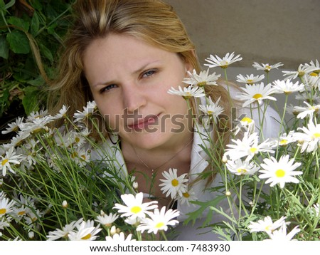 Blond girl with daisies on a sunny day - stock photo