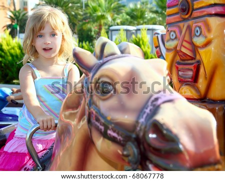 blond girl with fairground horse enjoy in park outdoor - stock photo