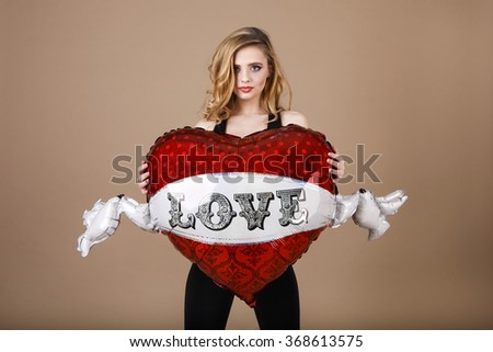Blond girl with red heart. Valentine's Day. Fashion beautiful woman with red heart balloon on a beige background. Close up of an attractive young woman holding a red heart. love - stock photo