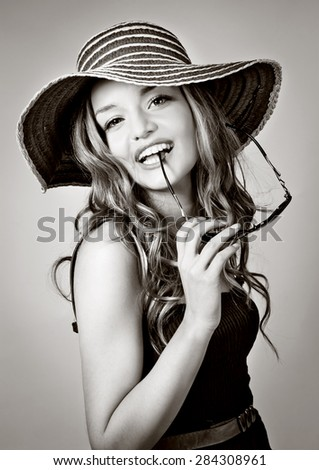 blond girl with summer hat and sunglasses  - stock photo