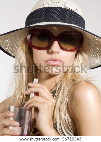 blond girl with summer hat and sunglasses posing and drinking - stock photo