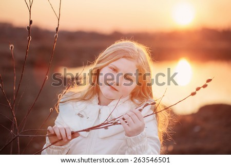 blond girl with willow on sunset - stock photo