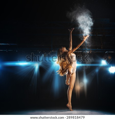 blond hair ballet dancer posing on stage in theater with powder - stock photo