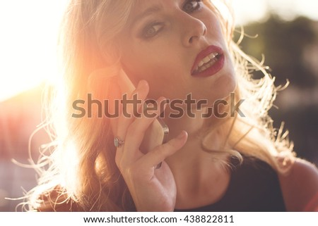 Blond hair girl using smart phone outdoors at sunset