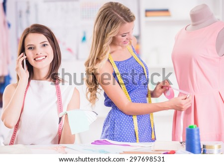Blond hair woman taking measurement with mannequin and brown hair woman speaking by phone in studio. - stock photo