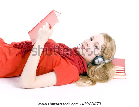 Blond hair young woman in headphones lying on pile of books - stock photo