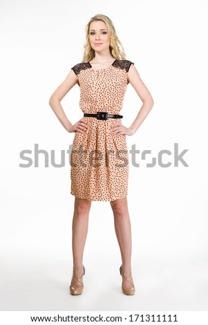 Blond haired business woman in beige summer dress isolated on white