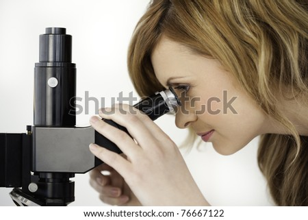 Blond-haired scientist looking through a microscope in a lab