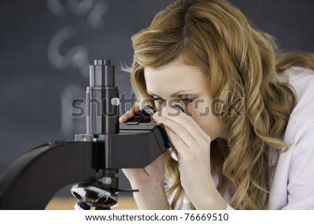 Blond-haired woman looking through a microscope in a laboratory