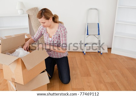 Blond-haired woman preparing to move house - stock photo