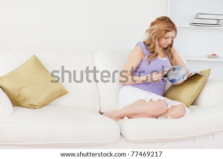 Blond-haired woman reading a magazine while sitting on the couch - stock photo