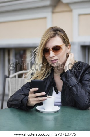 Blond haired young  woman with sunglasses sitting in the street cafe drinking a coffee and using a smart phone. - stock photo