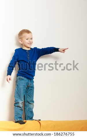 Blond happy boy preschooler standing on back rest of sofa and showing blank copyspace interior. Child kid playing at home. Childhood. - stock photo