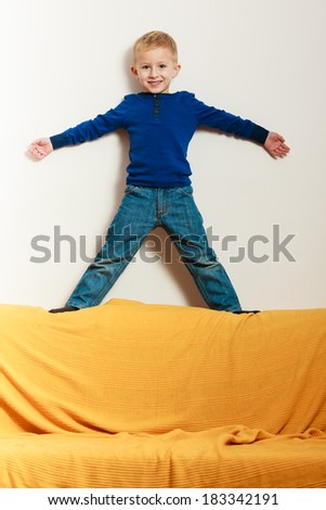 Blond happy boy preschooler standing on back rest of sofa interior. Child kid playing at home. Childhood. - stock photo