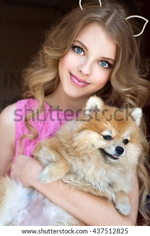 Blond happy girl with her doggy Spitz  - stock photo