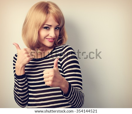 Blond happy young woman showing thumb up sign by two hands. Toned color portrait - stock photo