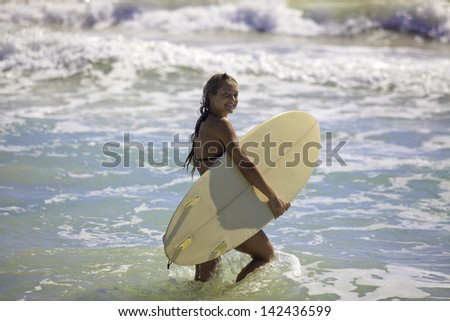blond in bikini with her surfboard heading into the waves in hawaii
