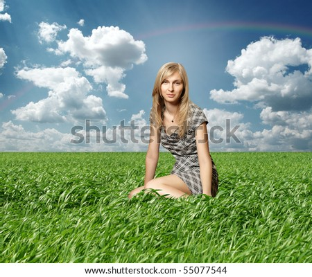 Blond in green grass on blue summer sky - stock photo