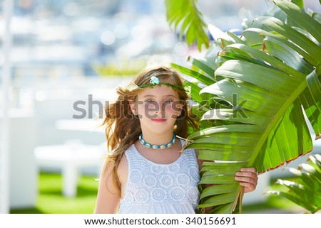 Blond kid girl at banana tree leaves in bright day light in Mediterranean - stock photo