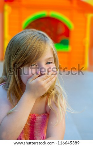 Blond kid girl funny gesture hand in mouth in playground with sundress - stock photo