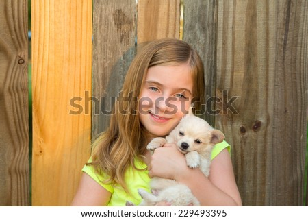 blond kid girl hug a puppy dog happy chihuahua in backyard wooden fence - stock photo