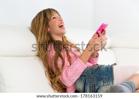 Blond kid girl playing fun with mobile smartphone on white sofa byod - stock photo