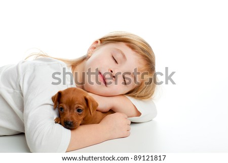 blond kid girl sleeping with mini pinscher pet mascot dog on white background - stock photo