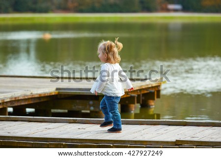 Blond Kid girl walking in the lake pier at the park - stock photo