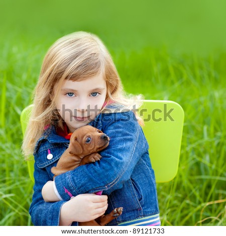 Blond kid girl with puppy pet dog sit in outdoor green grass - stock photo