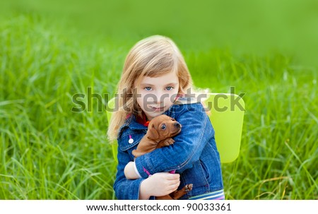 Blond kid girl with puppy pet dog sit in outdoor green grass