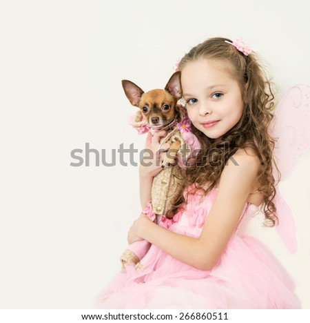 blond kid girl with small pet dog - stock photo