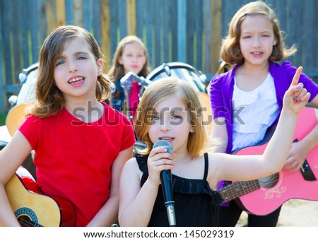 Blond kid singer girl singing playing live band in backyard concert with friends - stock photo