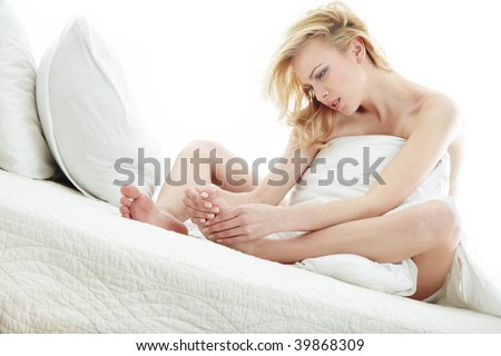 Blond lady covered by blanket in the bed room suffering from the callosity - stock photo