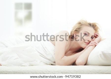 Blond lady laying in bedroom at early morning - stock photo