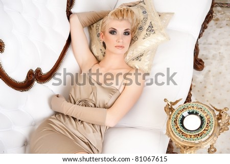 Blond lady lying on luxury sofa
