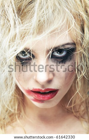 Blond lady with bizarre makeup and smeared lipstick on her face. Close-up photo. Natural colors