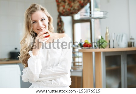Blond lady with ripe tomato at the kitchen
