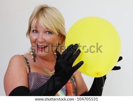Blond lady with yellow balloon and black gloves - stock photo