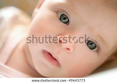 Blond little baby laying on bed portrait horizontal image - stock photo