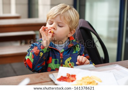 Blond little boy eating french fries in outdoor restaurant. - stock photo