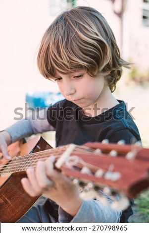 Blond little boy playing spanish guitar outdoors - stock photo