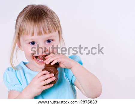 Blond Little Girl Eating a Messy Chocolate Easter Bunny - stock photo