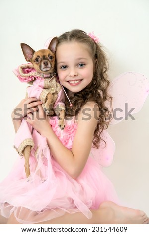 blond little girl in pink fairy costume holds small pet dog.  - stock photo