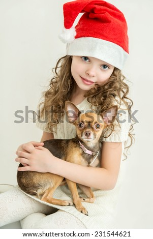 blond little girl in Santa Claus hat with small pet dog.  - stock photo