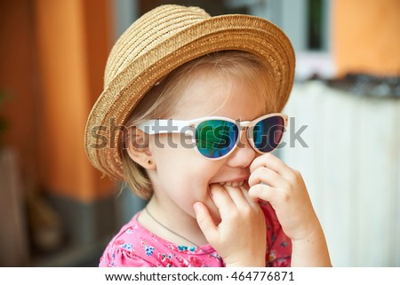 blond little girl portrait finger in nose gesture