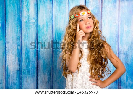 blond little girl thinking in vintage blue wood background - stock photo