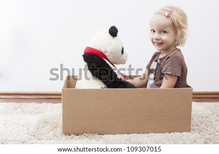 blond little girl with her teddy bear ready to move - stock photo