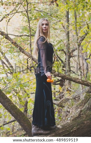 Blond long-haired girl in a fantasy black dress in an autumn forest, scary halloween fairy tale